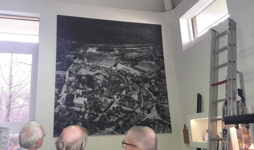 Medewerkers bekijken de zojuist opgehangen luchtfoto. Van links naar rechts: Gerhard Baan, Jan van de Maat en Dick Rietberg. Foto: Rijssens Museum.