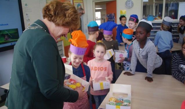 De burgemeester bewondert de prachtige cupcakes.