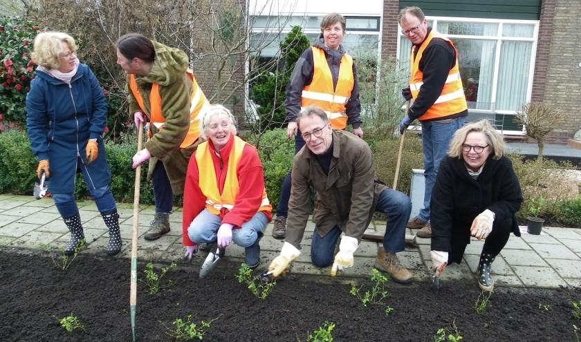 Sjoerd de Vries (midden) met buurtbewoners bij een plantvak met rode rozen. Zijn initiatief om het Reijerskoop op te fleuren, werd gesteund door de buurt en de gemeente Alphen.
