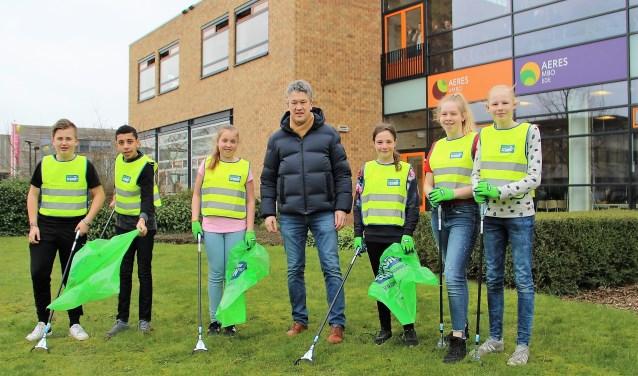 Wethouder Leon Meijer samen met leerlingen van Aeres VMBO Ede bezig met een schoonmaakactie rondom de school.