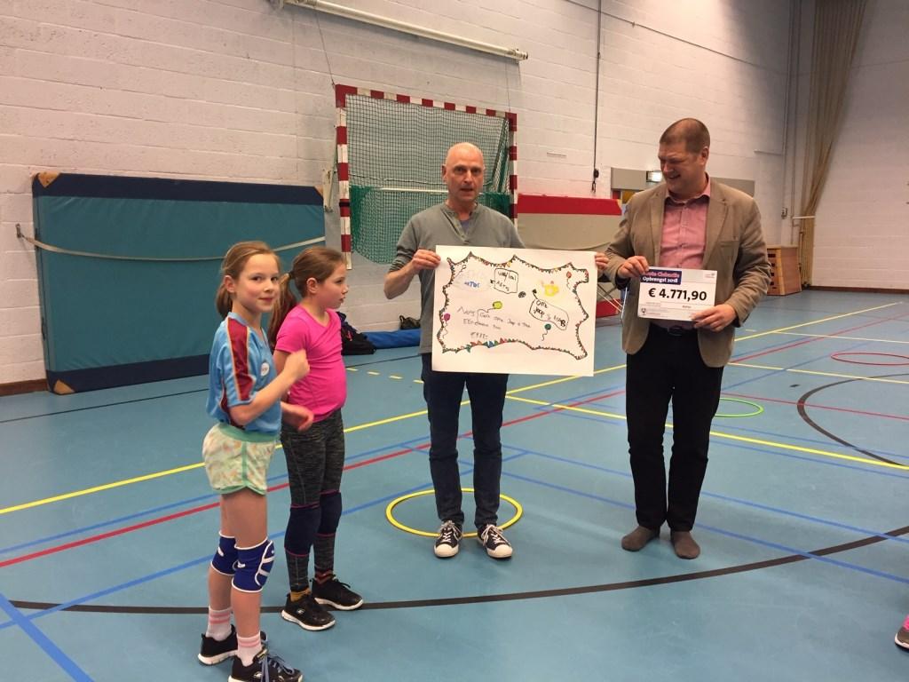 Yara (links), met haar zusje Tyche, overhandigen de zelfgemaakte cheque aan Vincent Leenders van Ome Joop's Tour  © Persgroep