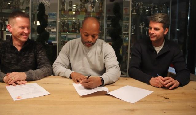 De nieuwe hoofdtrainer van Focus '07 Charly Olf tekent onder toezicht van Gijs Baars en voorzitter John Maassen zijn contract.