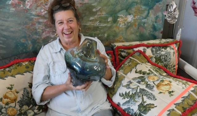 Ans Bakker in haar atelier met een van haar glasobjecten.