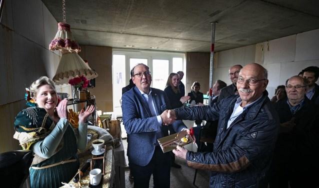 Wethouder Van den Bogaard (l) overhandigt aan een toekomstige bewoner de huissleutel.