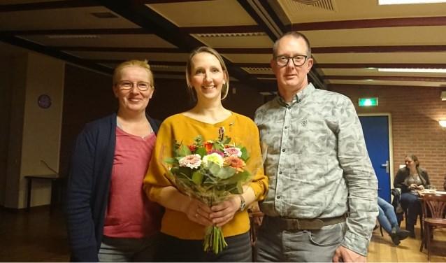 Voorzitter Martin Diepenmaat (rechts) heeft Martine Ooink de bloemen overhandigd. Links penningmeester Irene Werger.