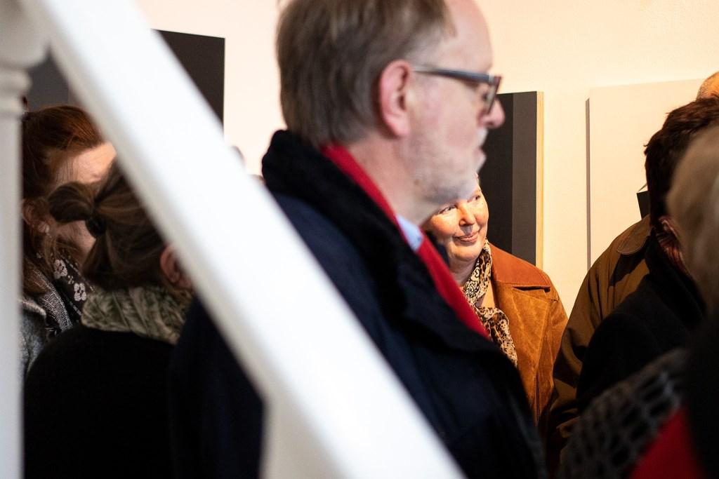 Bezoekers luisteren aandachtig naar het welkomswoord van galeriehoudster Monique Jasperse en kunstenaar Yvonne Willemse Foto: Ludo de Kort © Persgroep