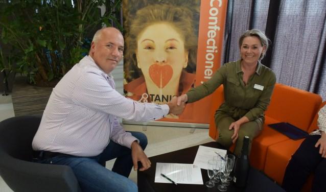 """Leo Tanis en Miranda van Rijswijk schudden elkaar de hand. Miranda: """"Samen met Tanis Confectionery kunnen wij een triathlon van topkwaliteit organiseren, waarbij hopelijk weer een mooie traditie ontstaat."""""""