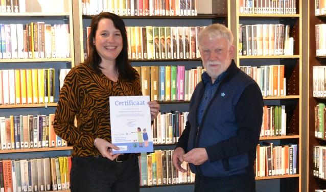 Bibliotheekmanager Claudia Toele krijgt het centificaat 'Dementievriendelijk' van trainer Jos van der Deure. (Foto: B.N.W.V.)
