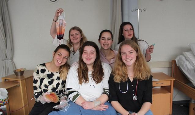 Richelle, Demi, Lisanne, Ans, Natalia en Evelien oefenen tijdens de praktijklessen op elkaar. Daarbij gebruiken ze verschillende attributen uit de zorg FOTO: MARIT JANSEN VAN GALEN
