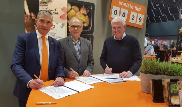 Voorzitter Eddie van Hattum (midden) ondertekent namens Algemene Hulpdienst Elst