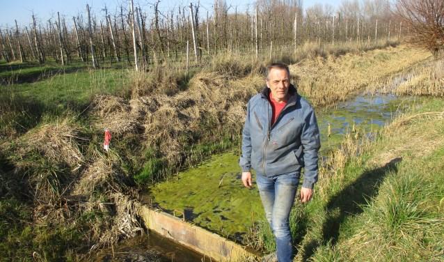 Bij een zelf aangelegde stalen stuw in de sloot vertelt Werner Louwerse hoe het werkt. FOTO: MARCEL VAN DER VOORT