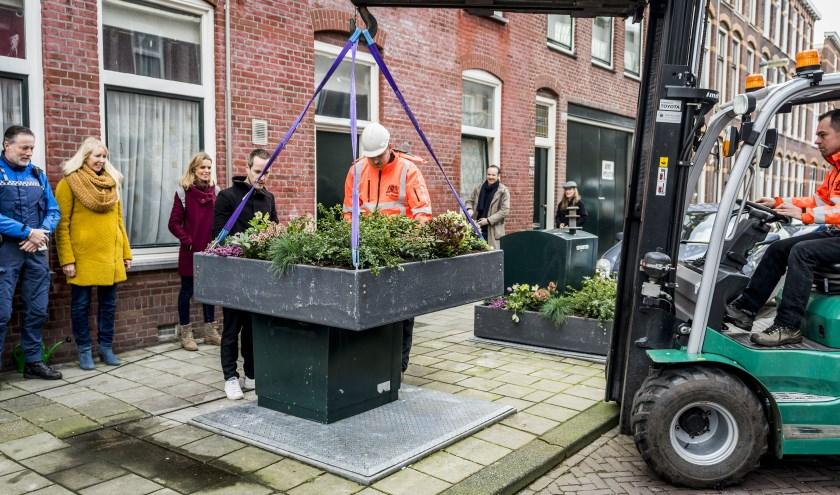 Wethouder Liesbeth van Tongeren (duurzaamheid) en bewoners kijken toe hoe het tuintje wordt geplaatst.