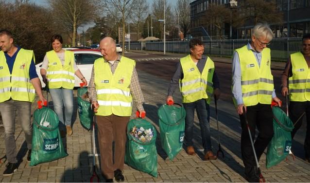 Vrijwilligers van Niacet BV prikken de Papesteeg schoon. (Foto: Bart van den Berg)