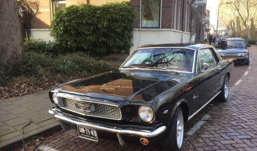 Een glimmende Ford Mustang staat geparkeerd aan de Boompjeswal.