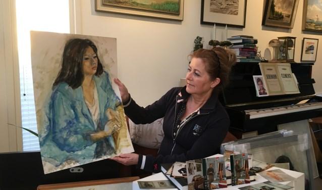 Marion met een portret dat ooit door haar vader werd geschilderd.