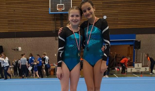 Onderschrift: Super blije DOS medaille winnaars Ilse (links) en Mika (rechts) samen op het podium.
