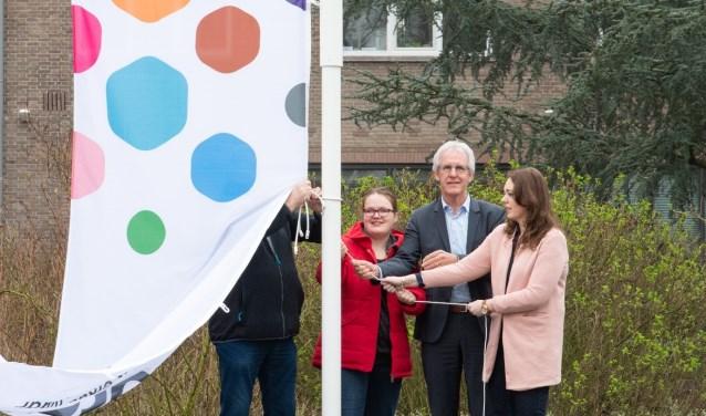 *Met trots hijst Anne Wolfsen (links) samen met Jan Duenk (bestuurder) en Bo Diemers (begeleider) de vlag, een mooi begin van de lente.