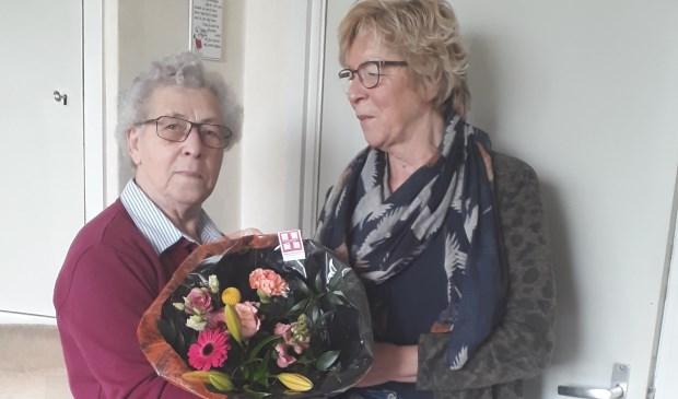 Femmi klein Wolterink ontvangt bloemen voor haar 50-jarig jubileum als collectant van ReumaNed.