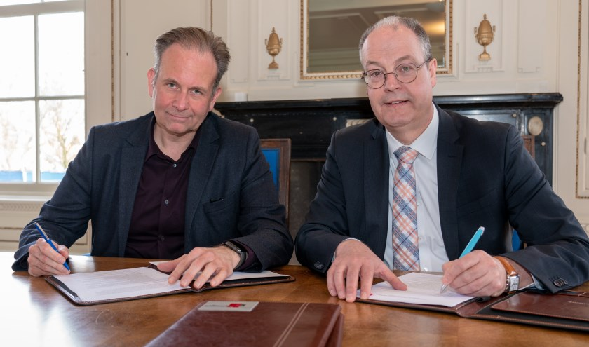 Wethouder Noël Vergunst van de gemeente Nijmegen (links) en wethouder Johan Sluiter van de gemeente Lingewaard ondertekenen de samenwerkingsovereenkomst. (Foto Fons Sluiter)