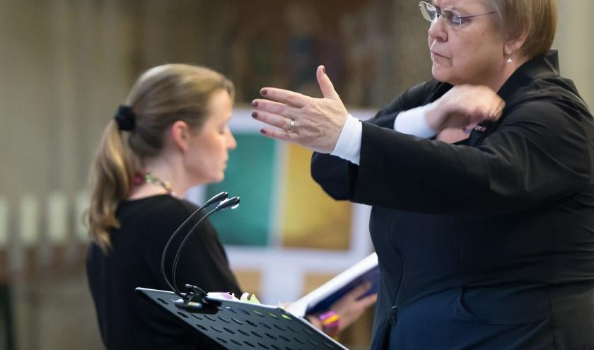 Dirigent zoals de koorleden haar zien, sprekend met handen en gezicht. Op de achtergrond sopraan Ilse Jordan