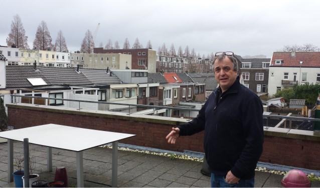 Adrie Brussé op het dakterras van zijn woning/bedrijf, waarop hij uitkijkt op de lager gelegen Oosterstraat.