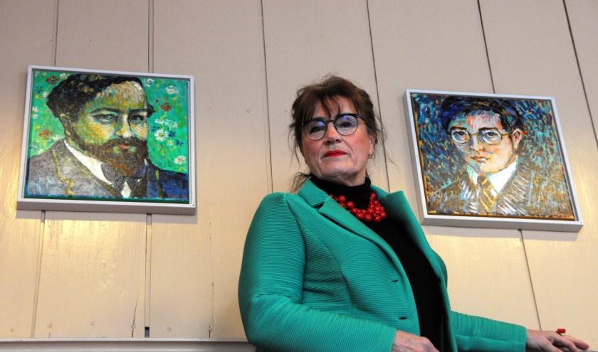 Roeli Rumscheidt temidden van twee door haar geschilderde portretten, Debussy (links) en Shostakovic. (foto: Voerman Museum Hattem)