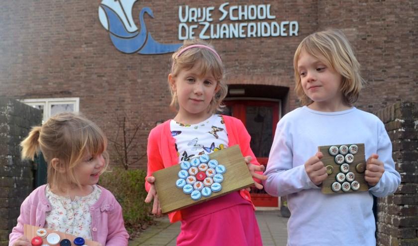 Suze, Ebba en Fosse hebben alvast geoefend met 'bottle cap art' voor de Lentemarkt op 30 maart. (foto: Gert Kootstra)