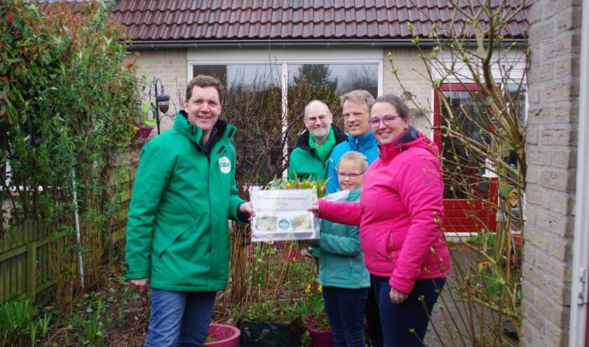 Maarten Jansen reikt de prijs uit aan Rixte en Meindert voor hun winnende tuin.