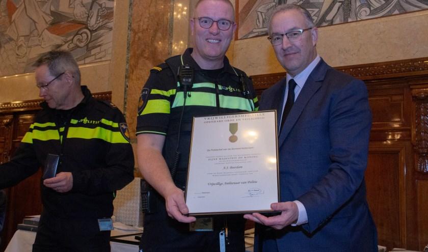 Met trots laat Arjo Boerdam zijn vrijwilligersmedaille openbare orde en veiligheid zien, geflankeerd door burgemeester Ahmed Aboutaleb van Rotterdam (Foto: Politie Rotterdam).