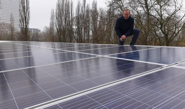 Bestuurder Bertjo Renzenbrink plaatst het laatste zonnepaneel.