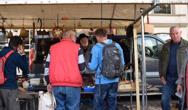 Bezoekers struinen langs gezellige kraampjes met rommelmarktspullen en curiosa. Eigen foto