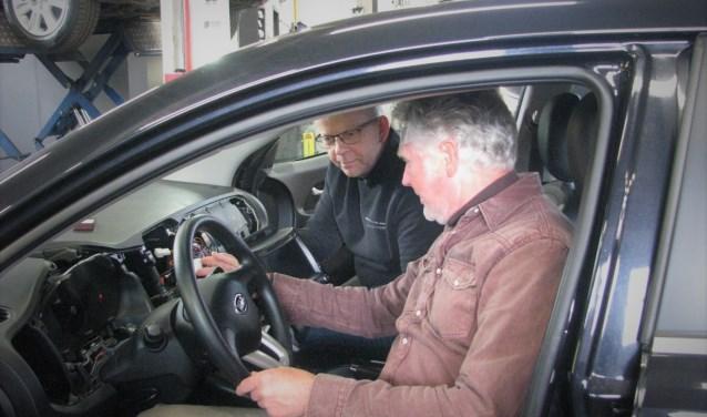 Vanachter het stuur sleutelt Ron van der Lem aan de laatste aansluitingen van een navigatiesysteem.