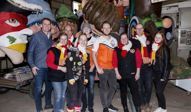 Rick van der Ven en Sjef van den Berg met de vrijwilligers van carnavalsbouwclub Ut Sepke en de praalwagen.