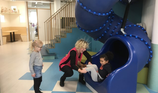 Directeur Jokelien Homans vangt een leerling op bij de glijbaan in de Propschool.