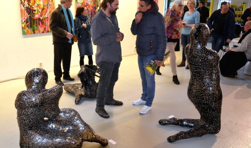 Kunstenaar Frans de Winter (vooraan links) in gesprek met een bezoeker van zijn tentoonstelling in Kade40. Hij staat te midden van drie van zijn kunstwerken. (Foto: Frans Assenberg)
