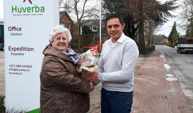 Raadslid Mimi Gunther overhandigd bloemen aan een medewerker van Huverba.