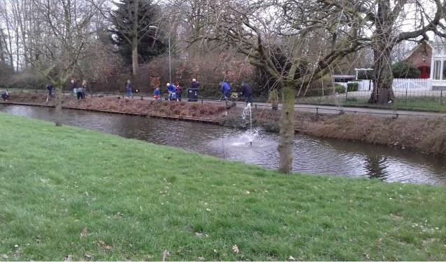 De vrijwilligers aan het werk langs het water.