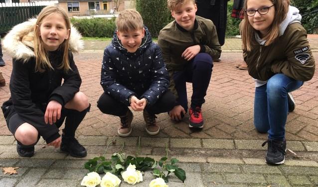 Vlnr: Rachel, Stijn, Rick en Noa, leerlingen van School met de Bijbel De Regenboog leggen witte rozen bij de gedenksteentjes. (Foto: pr)