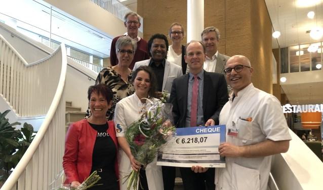 In de witte jassen onderzoekster Lina van der Straten en internist-hematoloog Mark-David Levin met tussen hen in oud-burgemeester Schrijer.