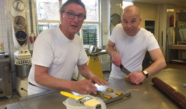 Baardwijk-voorzitter Dennis Vos bakt samen met bakker en sponsor Hans van Beijnen speciale jubileumkoekjes.