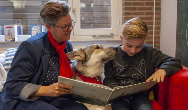 Floris Hulzink (9) op de bank in  de bibliotheek met voorleescoach Gerrie Pols en voorleeshond Hotch.