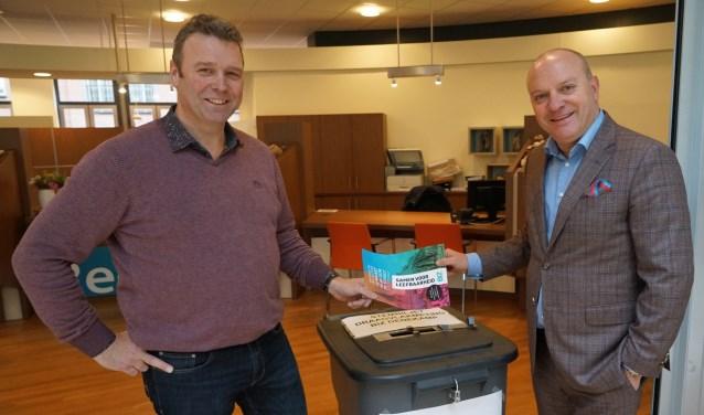 Wethouder Benno Brand en secretaris van de stichting BIZ Denekamp John Wigger bij de stembus in de hal van het gemeentehuis.