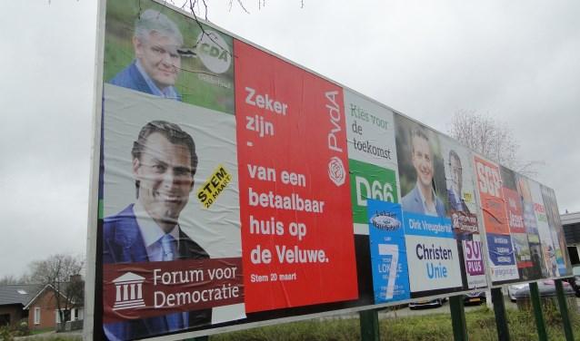 Bord met verkiezingsposters in het centrum van Stroe.