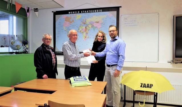 Vertegenwoordigers van ZAAP Rhenen overhandigen het scholenpakket. (Foto: Max Timons)