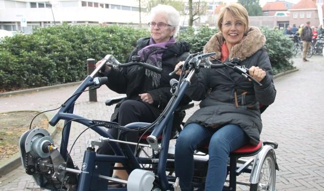Wethouder Tineke Zomer (r.) rijdt een rondje op de duofiets met Tiny Grotenhuis-Egbers bij de opening van het Samenrijderspunt (Foto: Lineke Voltman)