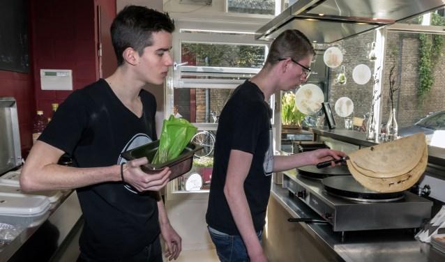 Bjorn en Kasper (voorgrond) aan het werk bij Crepes & Smoothies. (foto Auke Pluim)