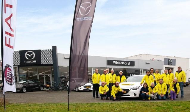 Een aantal vrijwilligers van het Vrijwilligerspunt en een aantal chauffeurs rondom de auto welke door garage Winkelhorst voor promotiedoeleinden is aangeboden.