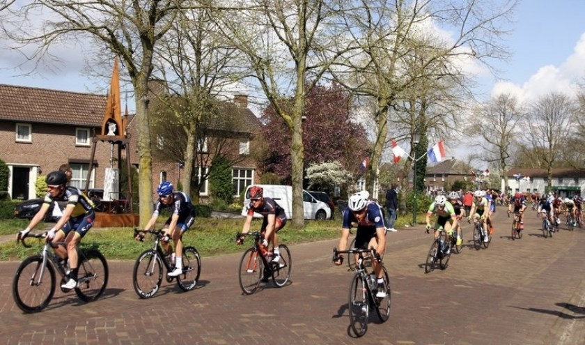 De renners komen langs het wielermonument aan de Vloetweg in Oploo (foto: Tunnis.nl)