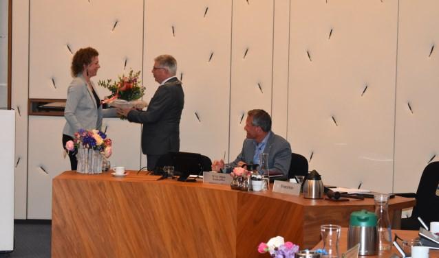 Cindy ter Riet overhandigt een bos bloemen aan burgemeester Henk Robben, als dank voor zijn inzet als voorzitter bij de raadsvergaderingen. Foto: Jolien van Gaalen.