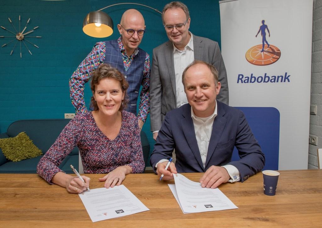 Economiedocent Ben Nijmeijer (links) en directielid Ben van den Anker van het Candea College kijken toe als Esther van Kraaij (Rabobank) en Niek den Tex (Scholenstrijd) de overeenkomst tekenen.